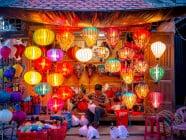 Local craftsman surrounded by colorful lanterns, at night, in Hoi An Ancient Town, Quang Nam Province, Vietnam
